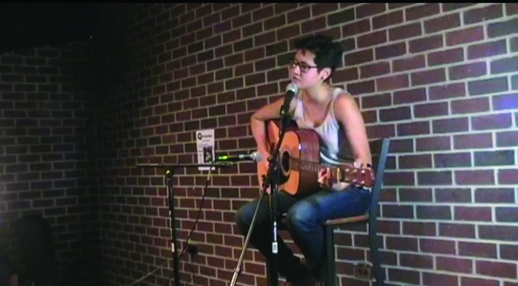 """Diana Muniz, FCLC '12, performs at the """"Q the Spotlight"""" event as part of Rainbow Alliance's 'Queer' awareness campaign. (Courtesy of Q the Spotlight!/YouTube.com)"""