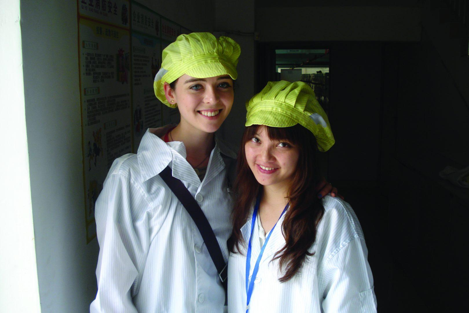 Heather Foye, FCLC '14, and Janet, her Chinese roommate, pose in smocks and hats in an electronics factory. (Courtesy of Heather Foye)
