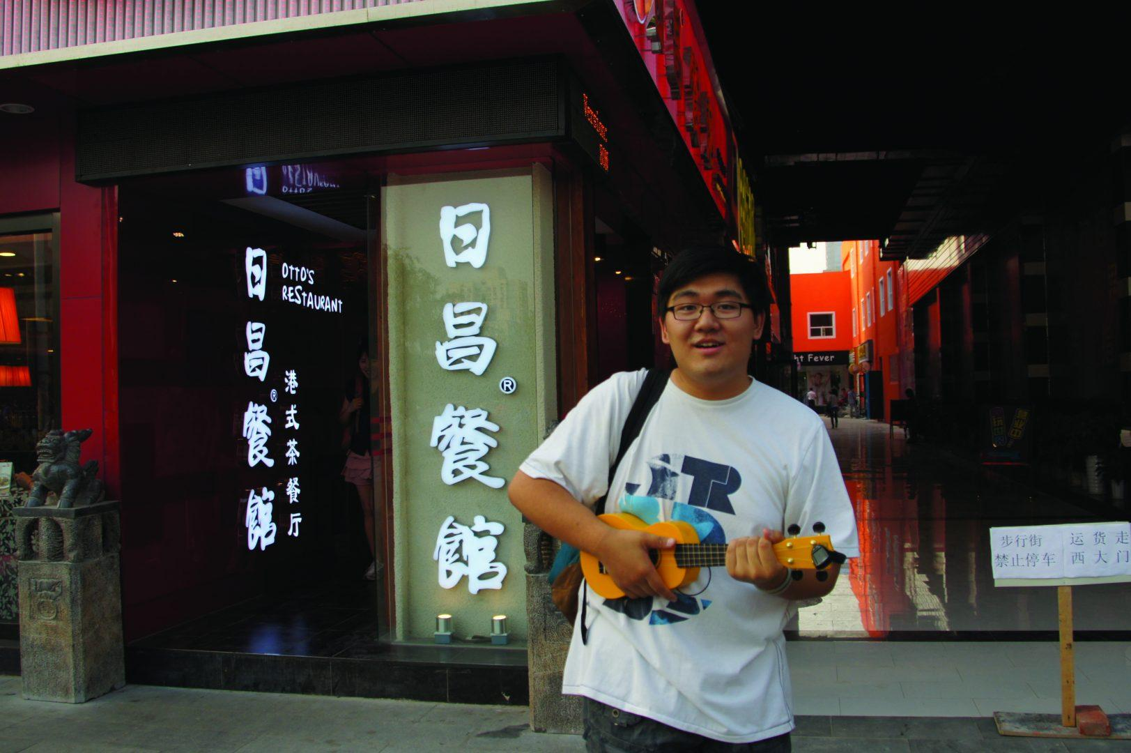 Tavy Wu, FCLC '16, poses with his ukelele in front of a restaurant in his native China.  (Photo courtesy of Tavy Wu)