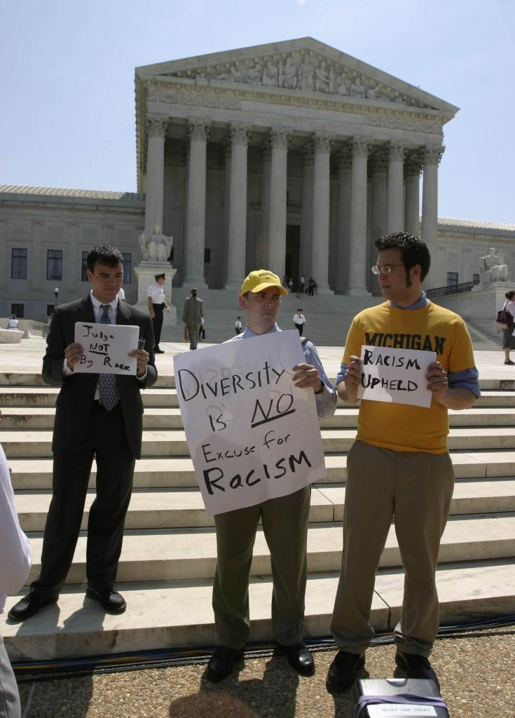 University of Michigan students, from left to right: Ruben Duran, James Justin Wilson, and Adam Dancy, all from Ann Arbor, Michigan, protest the Supreme Court's ruling on the use of affirmative action in college admissions, Monday, June 23, 2003 in Washington, D.C. In two split decisions, the Supreme Court ruled, on Monday, that minority applicants may be given an edge when applying for admissions to universities, but limited how much a factor race can play in the selection of students. (Chuck Kennedy/KRT/MCT)
