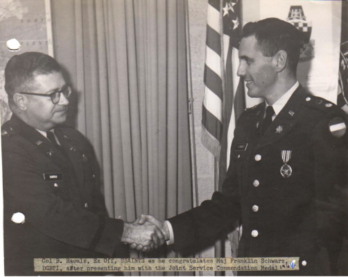 Caption reads: Col. B. Raouls, Ex Off, USAINTS as he congratulates Maj Franklin Schwarz, DCBTI, after presenting him with the Joint Service Commendation Medal, 1964. (Courtesy of Schwarz Family)