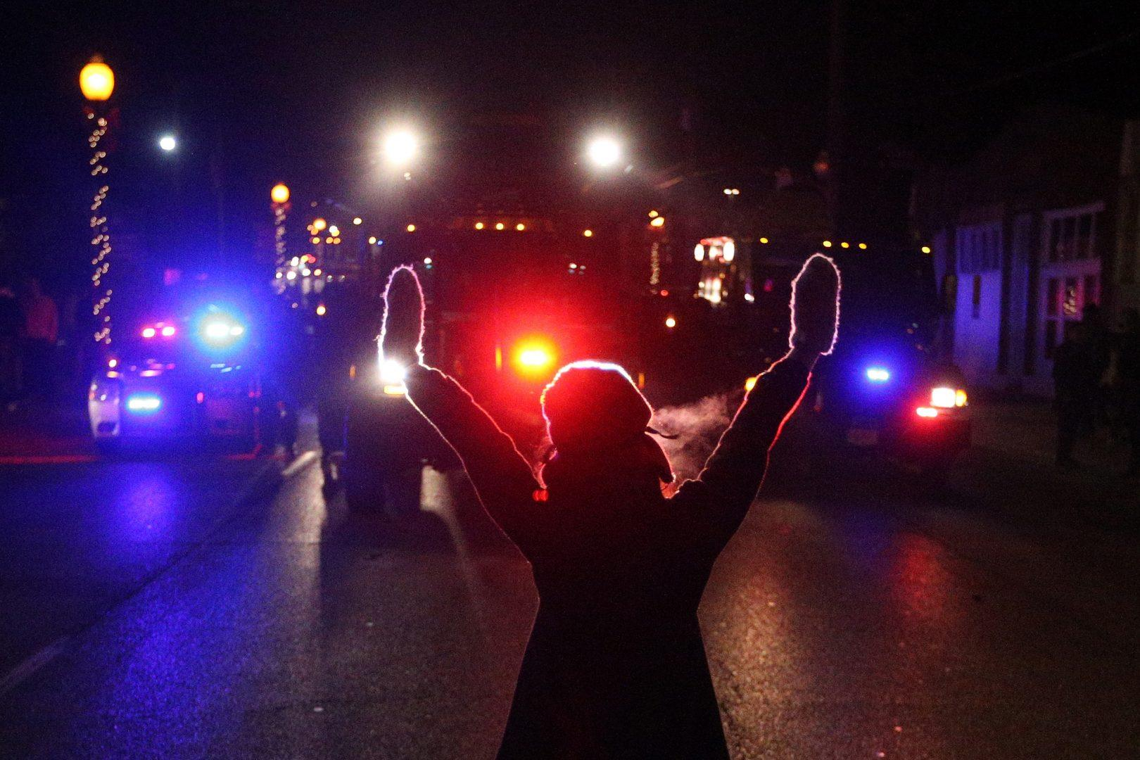 A protester raises her hands in the street as police use tear gas to try to take control of the scene near a Ferguson Police Department squad car after protesters lit it on fire on Tuesday, Nov. 25, 2014, in the wake of the grand jury decision not to indict officer Darren Wilson in the shooting death of Ferguson, Mo., teen Michael Brown. (Anthony Souffle / Chicago Tribune/TNS)