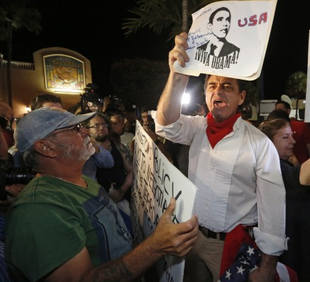 President Obama supporter Peter Bell, right, debates with anti-Obama demonstrators at Versaille's Restaurant in Miami on Wednesday, Dec. 17, 2014, after President Obama's decision to normalize relations between Cuba and the United States. (AL DIAZ/Miami Herald/TNS)