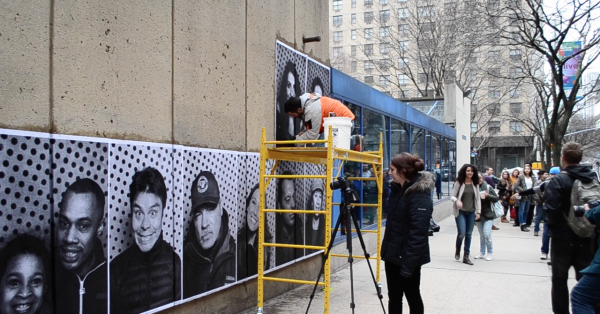 Artist+JR+pastes+the+photographs+for+his+Inside+Out+Project+on+the+wall+of+Fordham+College+at+Lincoln+Center.+Students+and+non-students+line+up+to+get+their+photo+taken+and+watch+JR+at+work+on+March+25%2C+2014.+%28Sri+Stewart%2FThe+Observer%29