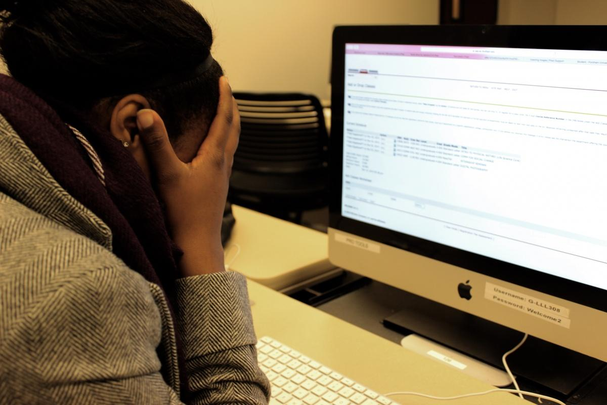 Fordham student Catrina L. hangs her head in frustration in a computer lab at Lincoln Center for the Spring semester. (PHOTO ILLUSTRATION BY ZANA NAJJAR/ THE OBSERVER)