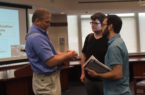 Graduate students, Steven Payne (left) and Alex Elnabli (right) speak with Bunsis. (ELIZABETH LANDRY/THE OBSERVER)