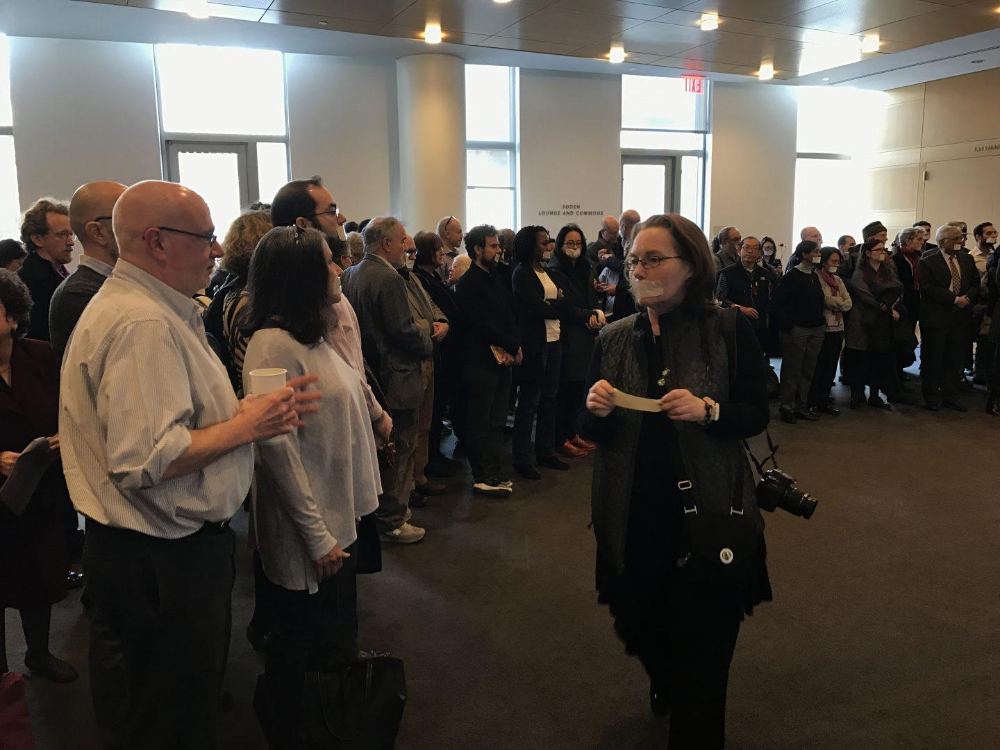 Over+100+faculty+members+holding+a+silent+protest+over+statutes+violations+outside+of+the+Board+of+Trustees+lunch+in+the+Bateman+Room+of+the+Fordham+Law+building.