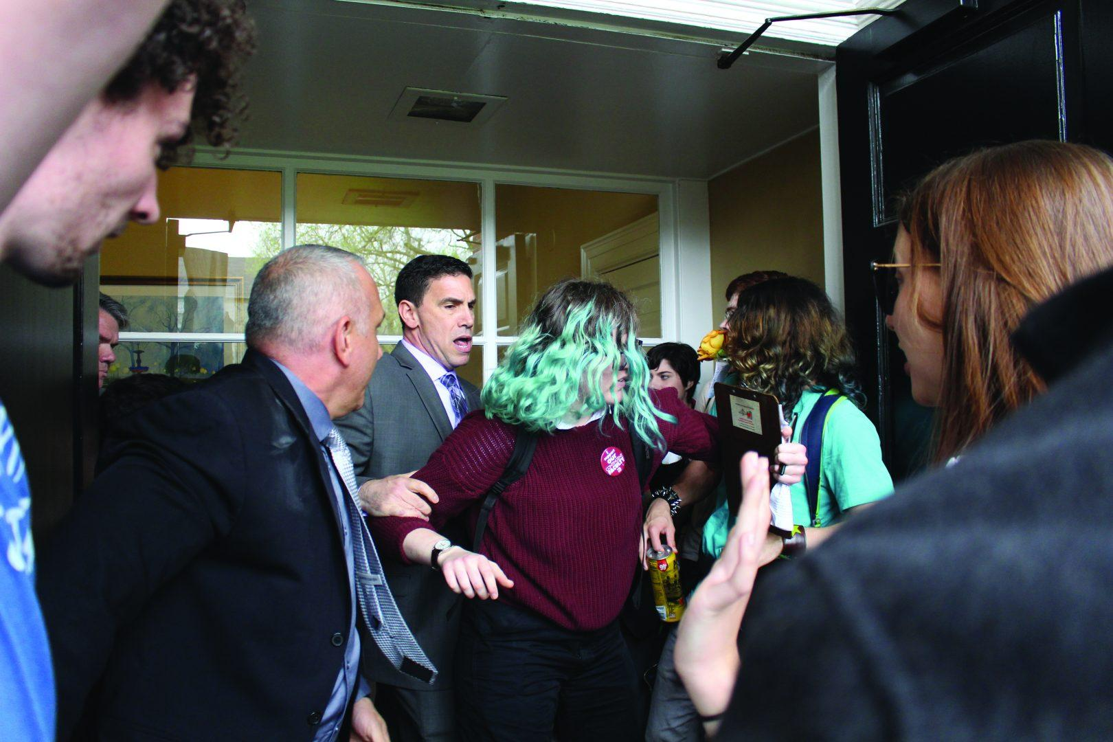 Student protester Sapphira Lurie, FCLC '17, is blocked from entering a door by Public Safety supervisors at Cunniffe House at Fordham Rose Hill. (GEORGE HORIHAN/The Observer)