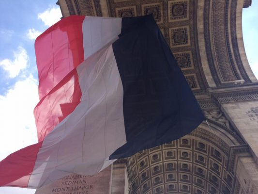 A large French flag waves in the wind from the center of the Arc de Triomphe. (MORGAN STEWARD/ THE OBSERVER)