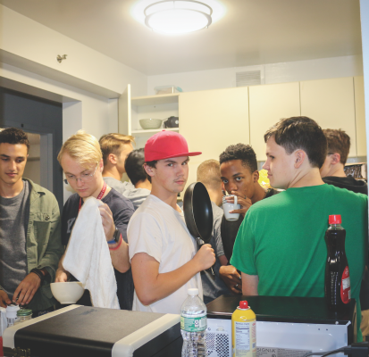 Freshmen in a nine-person suite cook dinner in close quarters. (Matt LaBarbera/The Observer)