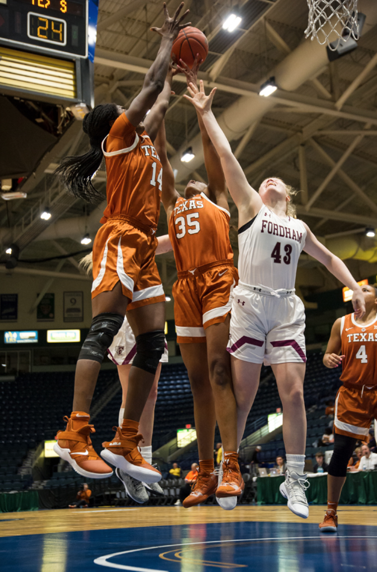 Megan Jonassen, Fordham College at Rose Hill '22, (right) reaching for a jump ball while playing against University of Texas. Photo courtesy of Kevin Bires