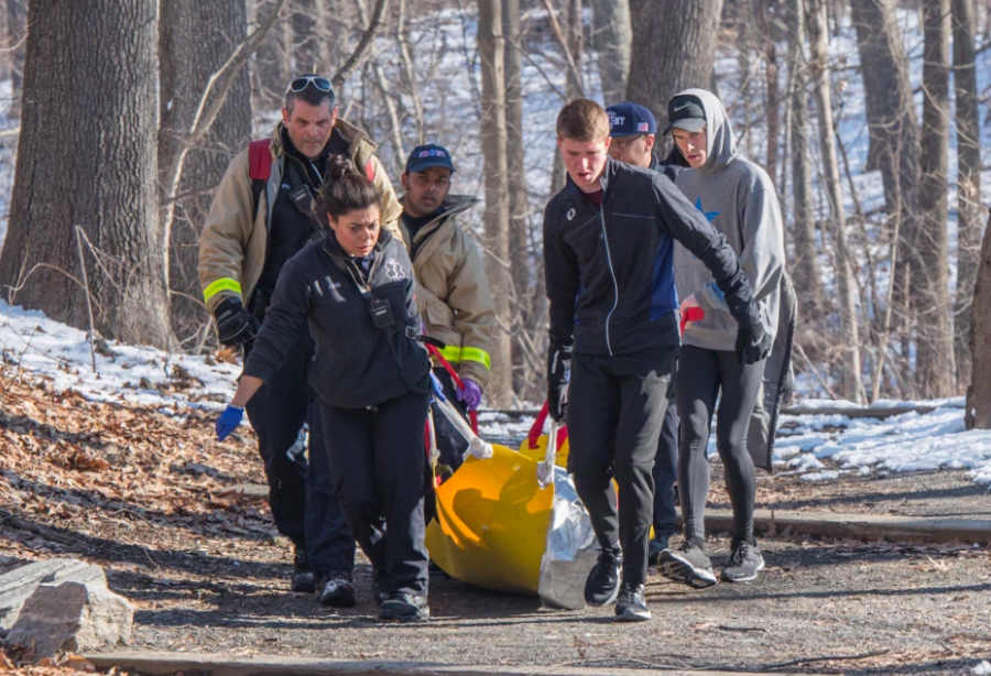 Fordham University runners assist FDNY EMT responders with rescuing a man in a Bronx park.