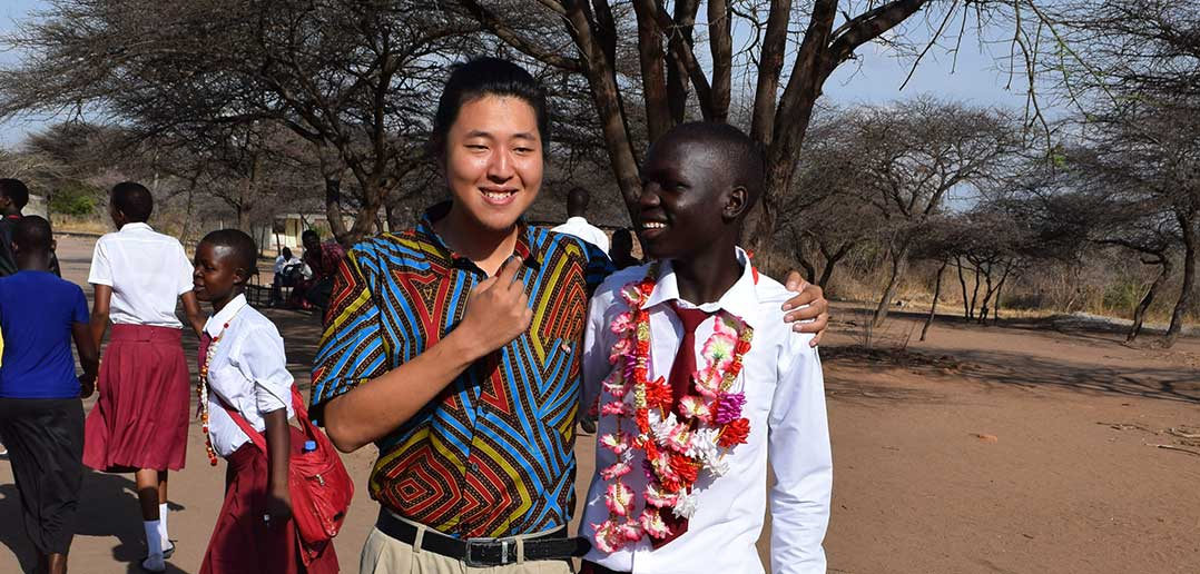 Kang Lee, FCLC '14, volunteering in Tanzania, pictured with one of his students.