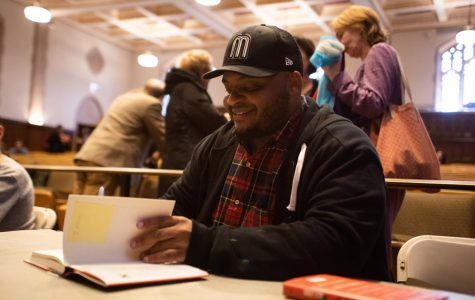 Kiese Laymon signs Fordham students' copies of his memoir,