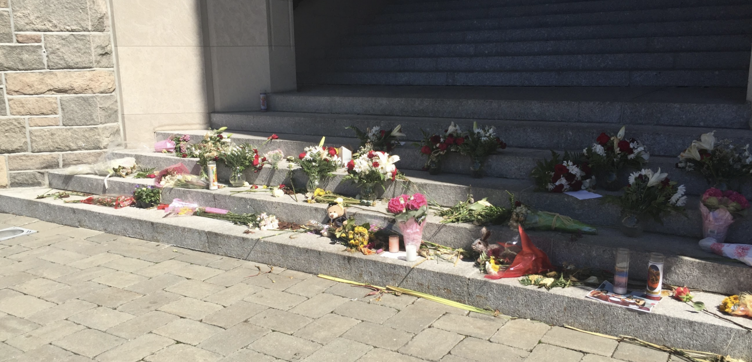Photos, candles and flowers line the steps of Keating Hall, the building where the accident occurred, to honor the life of Sydney Monfries.