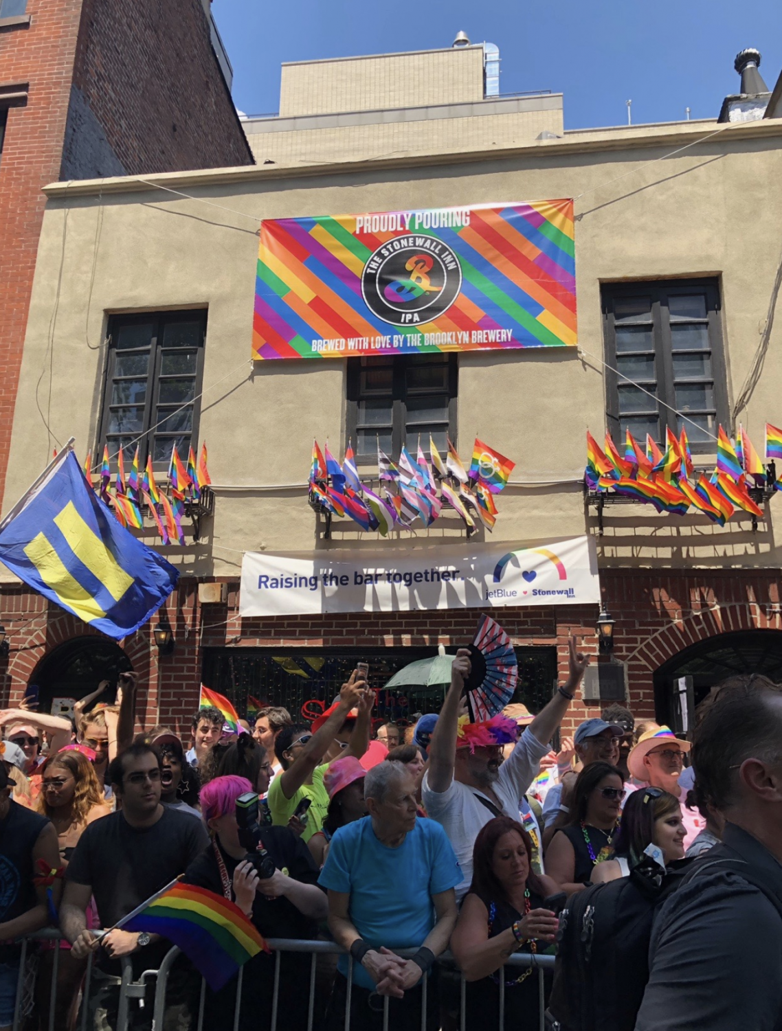 Pride participants celebrating outside of The Stonewall Inn, where the modern gay rights movement began in 1969.