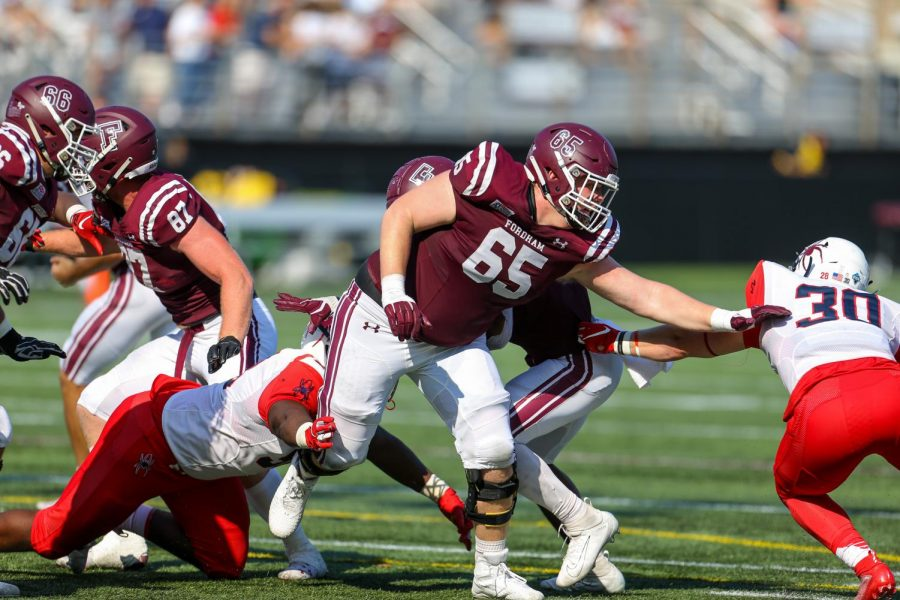 Offensive lineman Ryan Joyce, Fordham College at Rose Hill (FCRH) '23, blocks for quarterback Tim DeMorat, FCRH '22 against Richmond defenders.