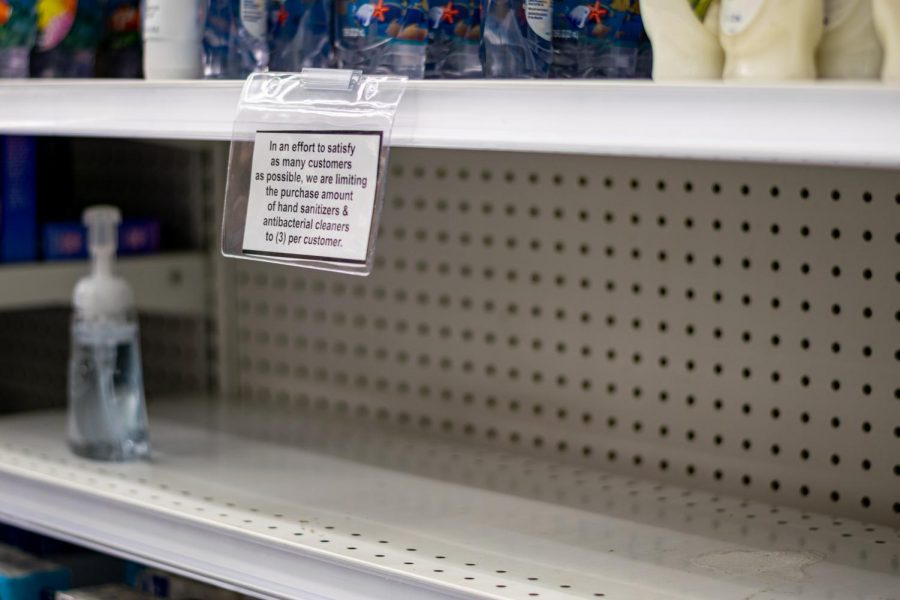 An empty shelf formerly holding hand sanitizer with a sign that limits hand sanitizer and antibacterial products to 3 per customer