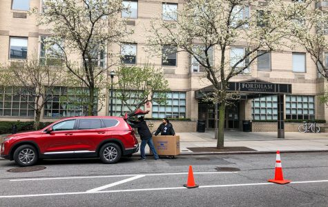 A red car with the rear hatch open as two people pack it with moving boxes in front of McMahon Hall