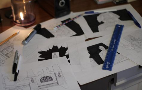 Storyboards of Koty Vooys' latest film are spread out across a table with pens and a ruler on top of them.