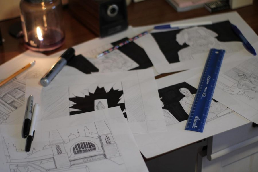 Storyboards of Koty Vooys latest film are spread out across a table with pens and a ruler on top of them.