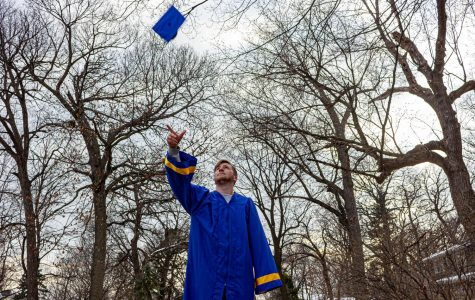 a student wearing a blue graduation gown and throwing a cap into the air