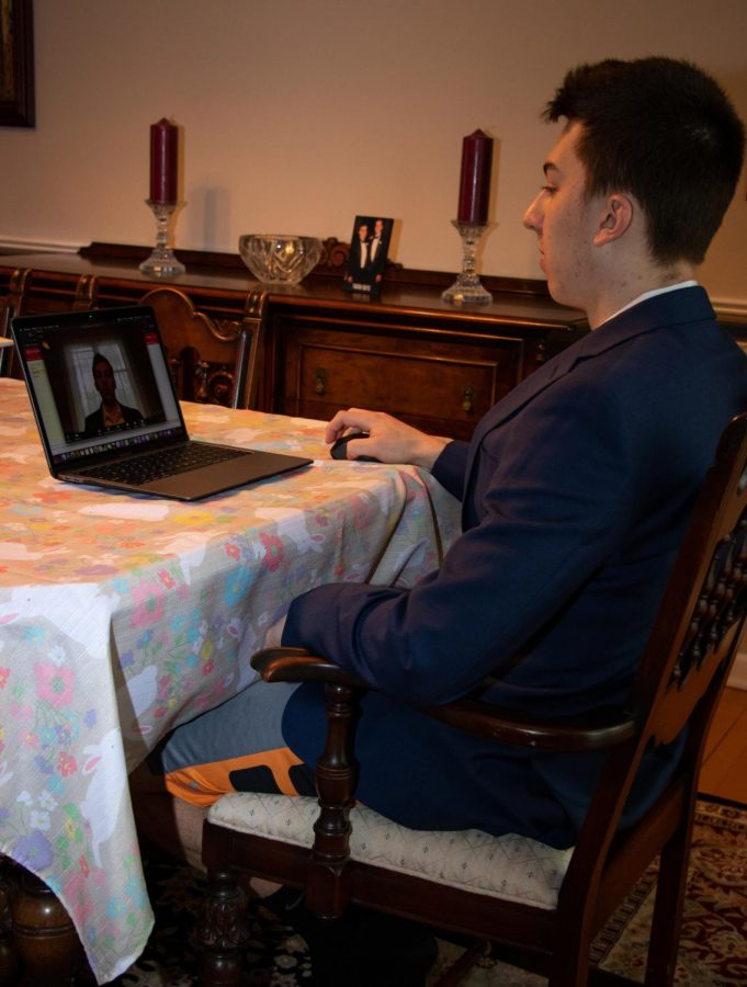 a student wears a suit while sitting at a kitchen table in front of an open laptop