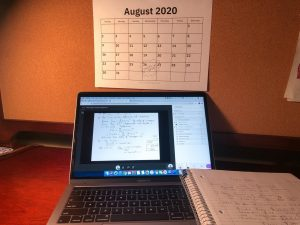 an open laptop in front of a wall calendar