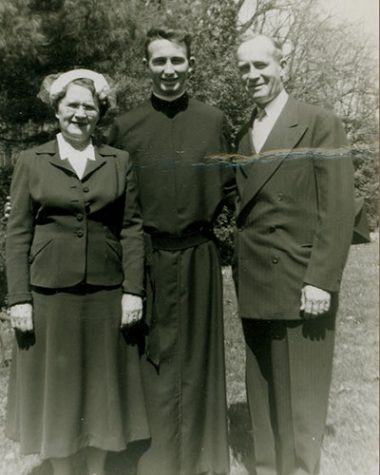 Black and white family photo with a young Fr. O'Hare in the center, his mother to his right, and his father to his left