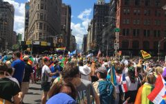 A colorful celebration in the streets of New York City during Pride March 2019. Flags from all over the world can be seen.
