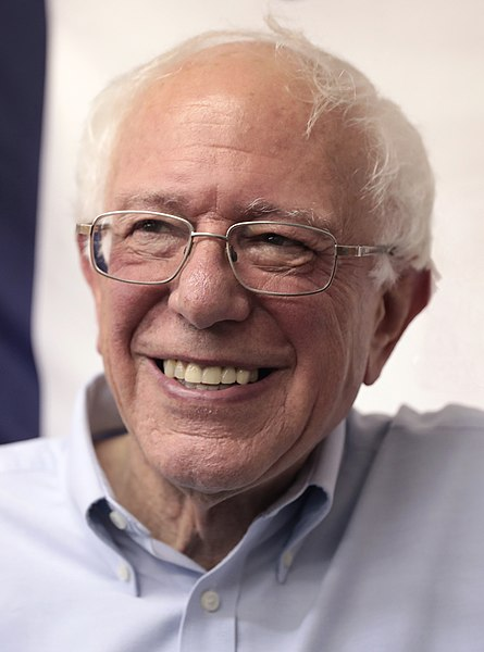 Up-close shot of Bernie Sanders smiling in glasses and a white collar shirt