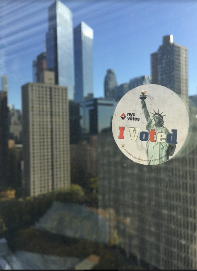 An+%22I+Voted%22+sticker+stuck+to+a+window+in+McKeon+Hall+overlooking+midtown+Manhattan
