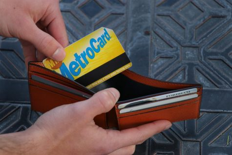 a NYC metrocard being pulled out of a wallet with a Fordham ID in it