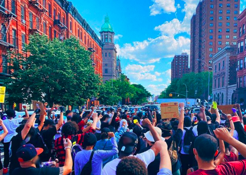 a crowd protests in the Bronx with fists raised