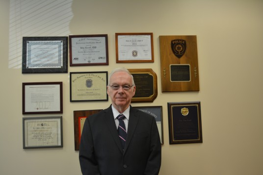 John Carroll photographed wearing a suit in his office with plaques of degrees and awards behind him