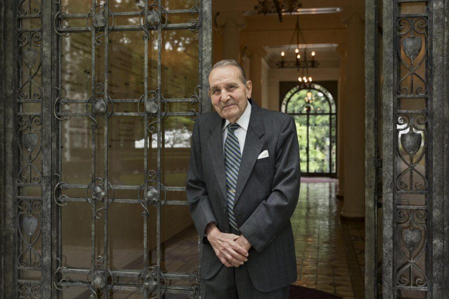 Cammarosano standing in a suit in tie in front of a glass door