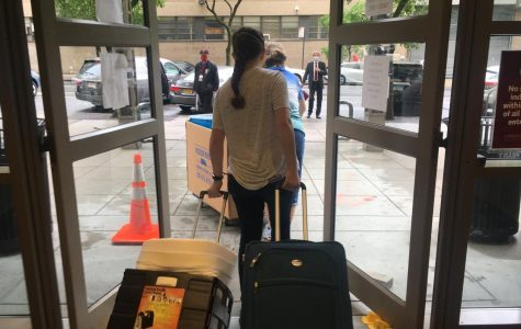 a student walks out of the doors of McMahon Hall while dragging two suitcases behind her