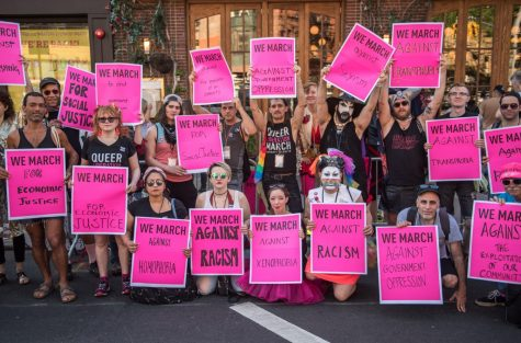 attendees holding up posters at the Queer Liberation March