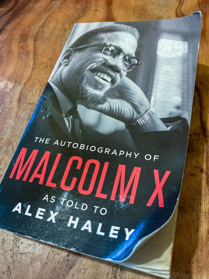 A+photo+of+%22The+Autobiography+of+Malcolm+X+as+Told+to+Alex+Haley%22+on+a+table.+The+cover+portrays+Malcolm+X+smiling+with+his+hand+on+his+face.