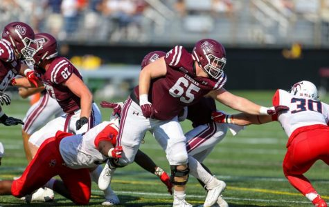 Fordham football player #65 reaches his arm out to block a member of the opposing team