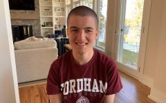 photo of male freshman student sitting in his home with a fordham t-shirt