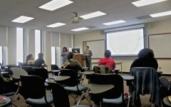 Fordham classroom with students sitting at desks facing a whiteboard, photographed from the back
