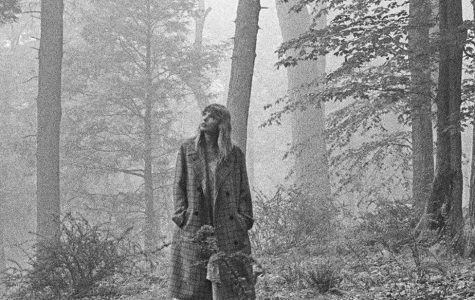 folklore album cover; taylor swift standing in the woods in black and white