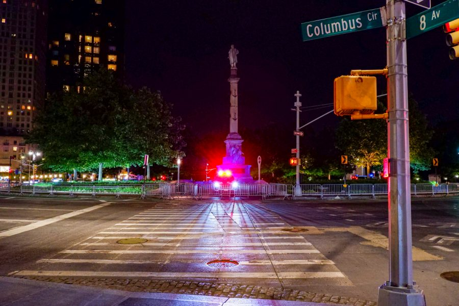 an NYPD cruiser with its lights on sits in front of the Columbus statue at night