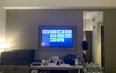 a hotel room, including a TV with Netflix, Crackle and YouTube icons on it, water bottles, a table and a couch