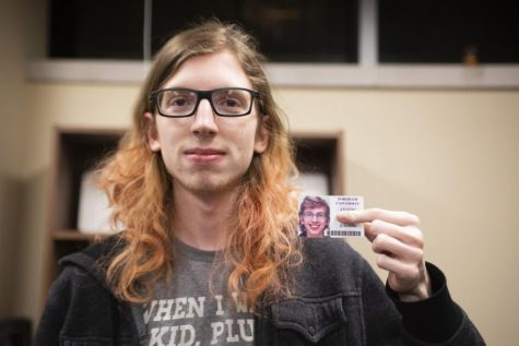 a transgender student holding their ID up for the camera while covering their dead name with their finger