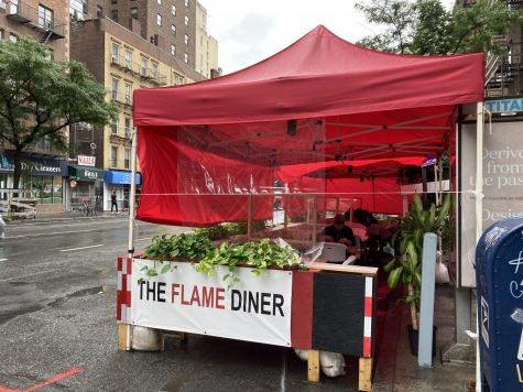 "red tent with sign that says ""the flame diner"" on a street"