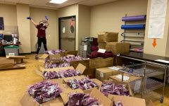 girl with gloves standing in front of boxes filled with maroon Fordham shirts for orientation