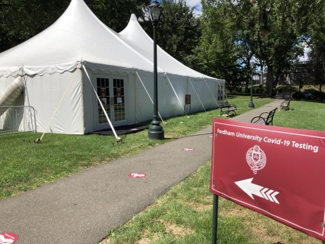 picture of white tents with a red sign in front indicating the tents are for coronavirus testing
