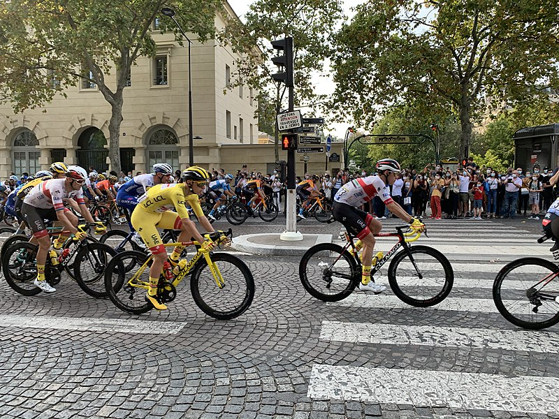 group of cyclists riding on a cobblestone street in the tour de france